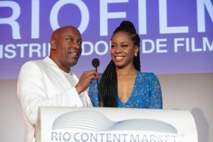 O diretor John Singleton e a atriz Danielle Moné Truitt, convidam a plateia para assistir à estreia mundial da série 'Rebel', que teve estreia mundial logo após a cerimônia de abertura do RioContentMarket.
